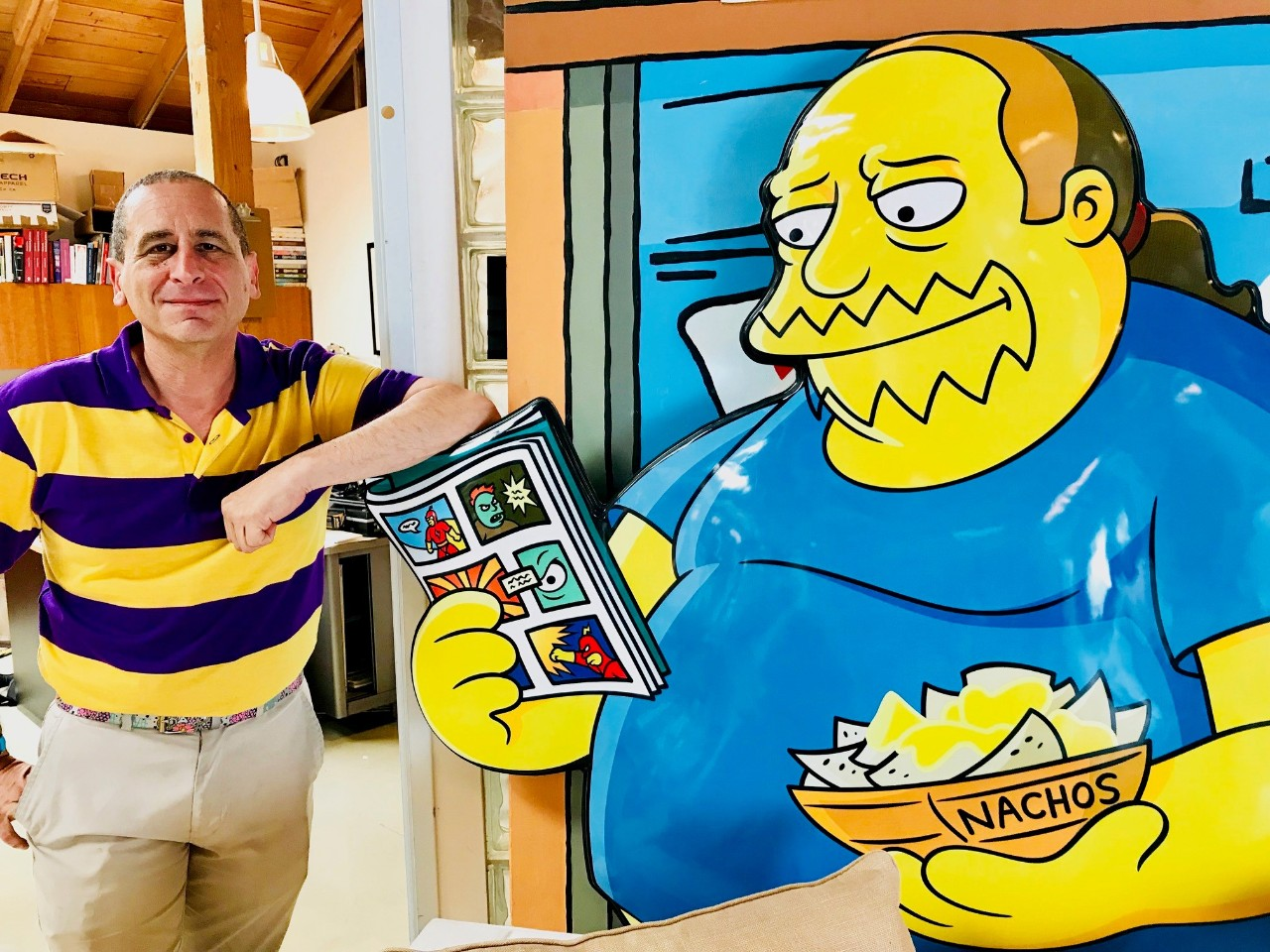Mike Reiss, writer for The Simpsons, next to his cartoon drawing of the writer.