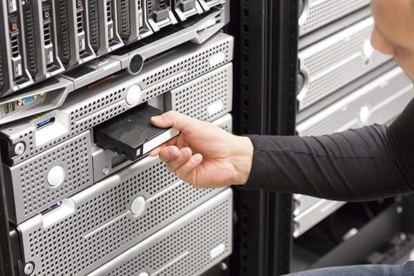 IT administrator puts magnetic tape cassette into data center memory system.