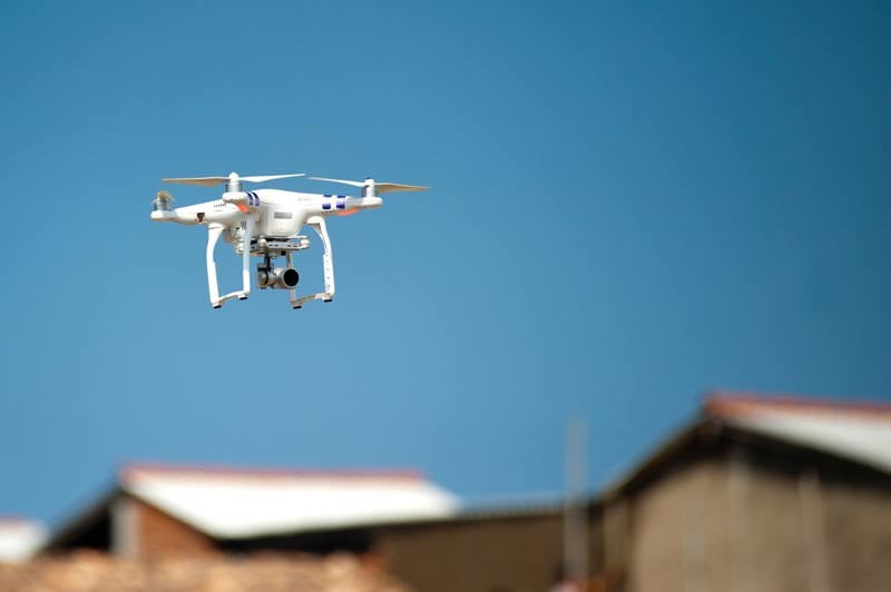 Drone flying over rural buildings.