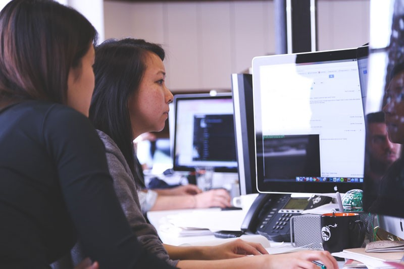Two women collaborating at a computer screen.