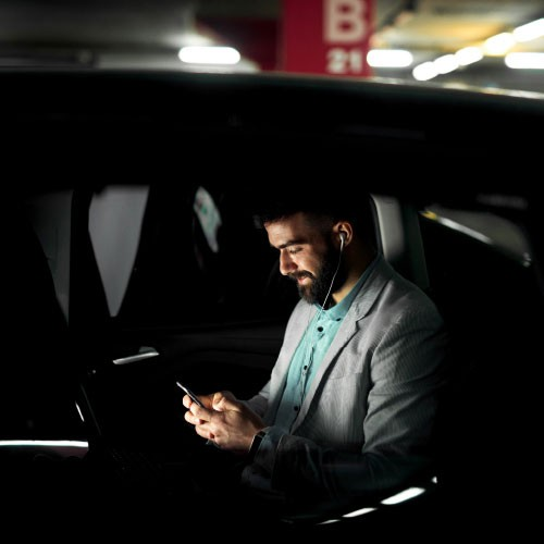 A picture of a man sitting in a car looking at his phone