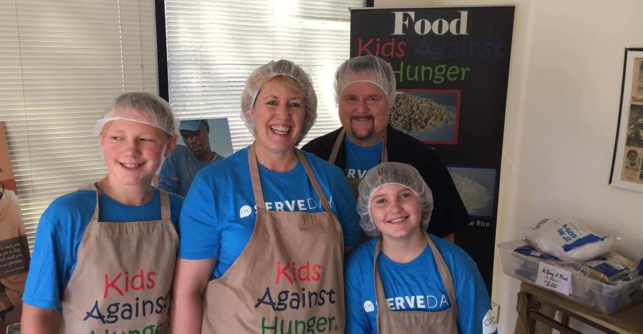 Wendy M. Pfeiffer with her family volunteering at Kids Against Hunger.